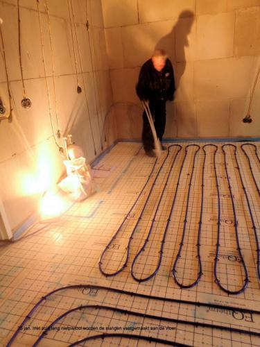 25 januari 2019: met een lang nietpistool worden de slangen vastgemaakt aan de vloer